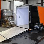 open back of orange and black single axle trailer